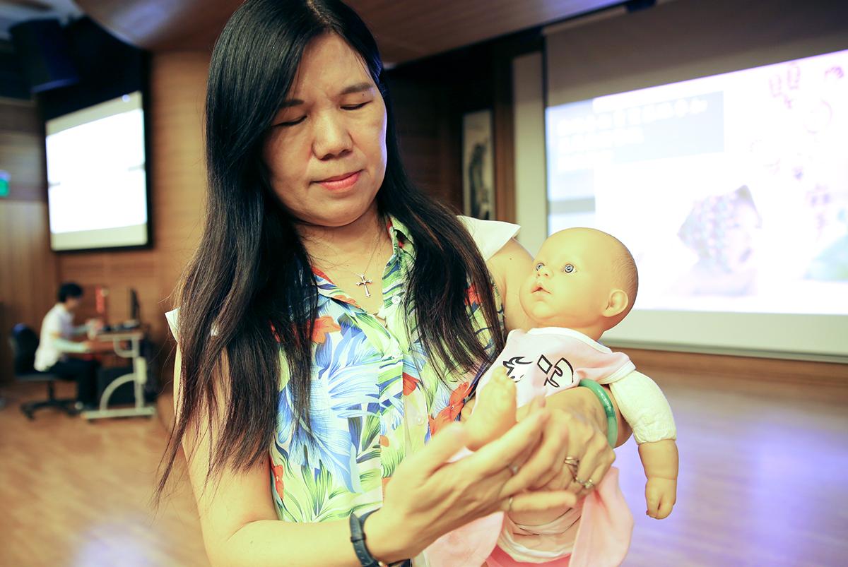 臺東大學幼兒教育學系副教授施淑娟,示範嬰兒腳部按摩。
