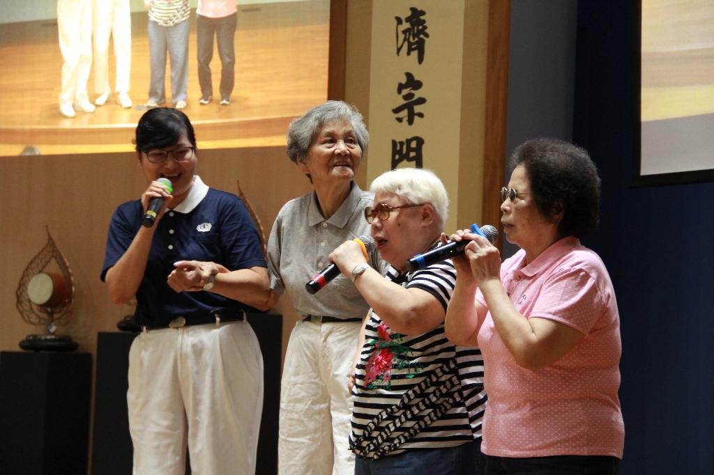 志工洪秉妍及兩位視障獨老長輩陳秀榮、林蘇霞合唱〈阿母的手〉。秀蓉把前來關懷的洪何桃阿嬤當成自己的母親。每個月的訪視,都希望她能多留一些時間。(攝影/謝昭光)