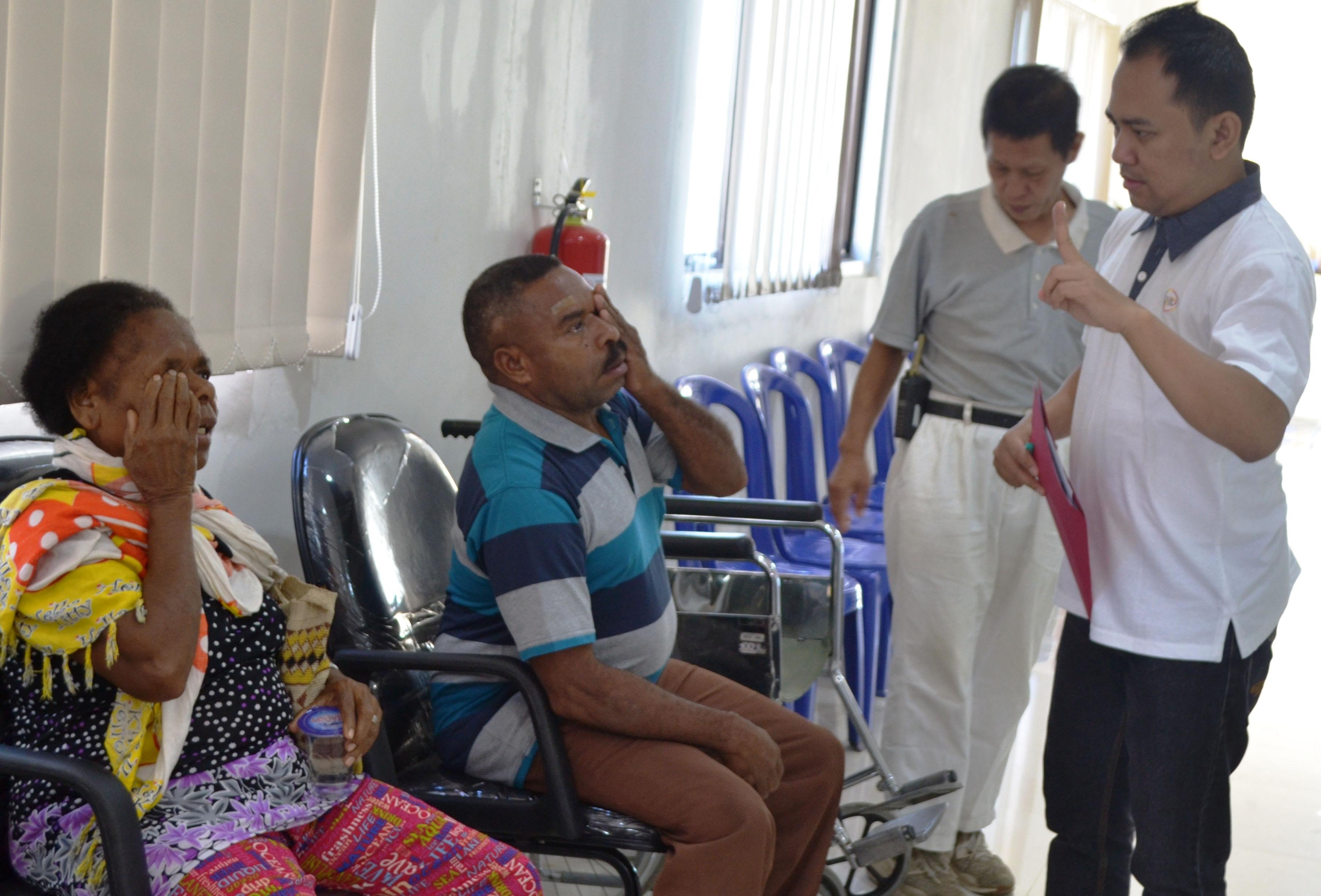 完成手術治療的病患瑪莎(Martha Basna,左),護士揭開她左眼紗布後,進行視力測試。