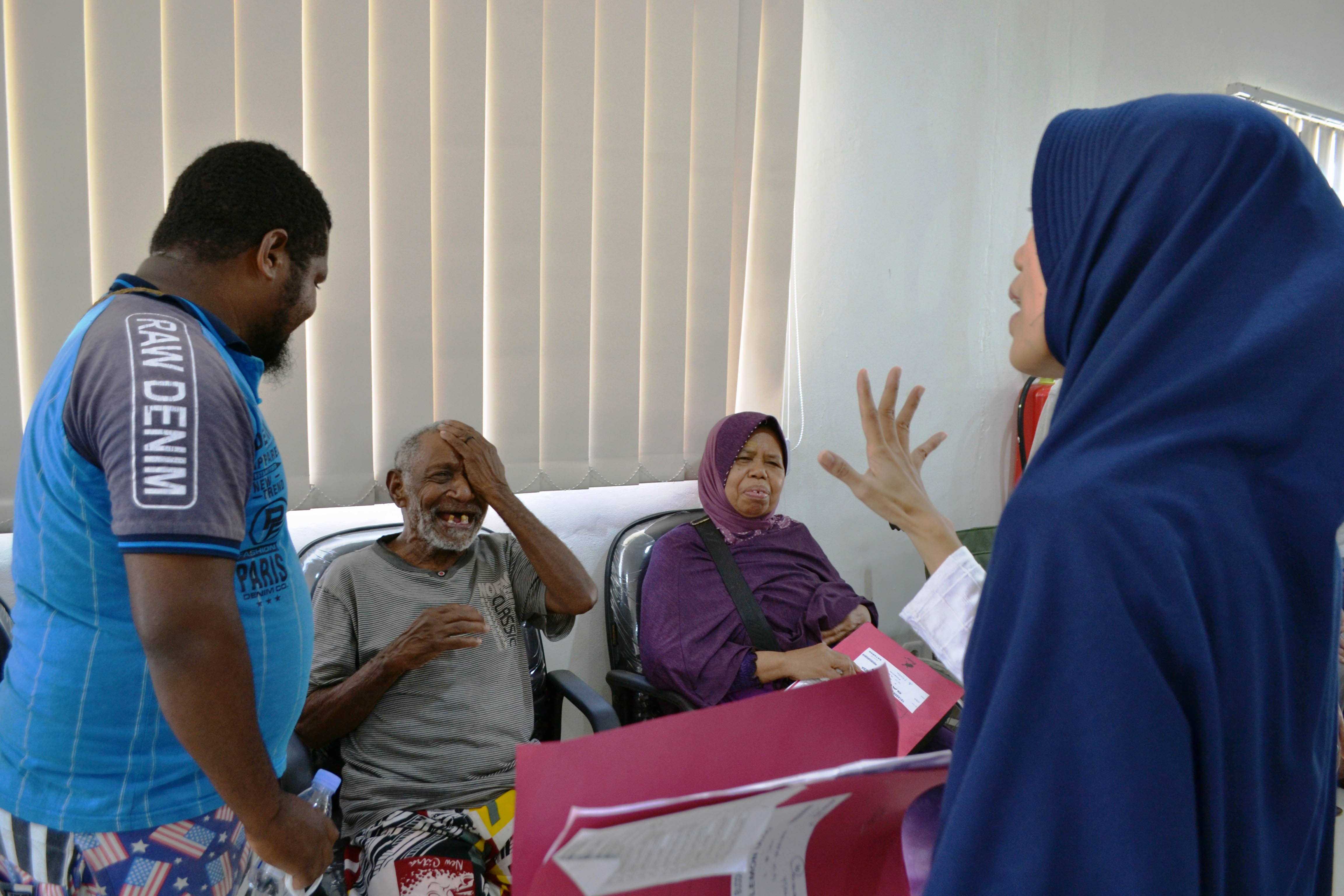 完成手術治療的飛樂夢(左二),護士為他進行視力測試,重見光明的他笑開懷。