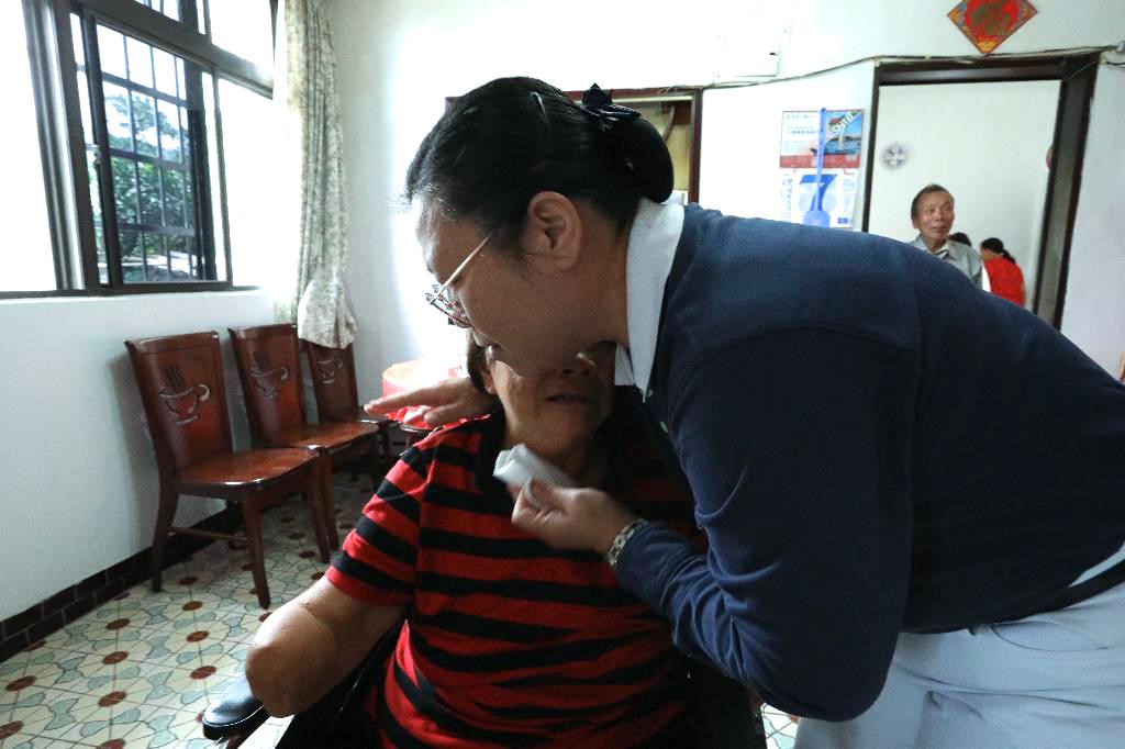 雙手雙腳截肢的阿嬤,因為行動不便,無法前往醫院探視眼睛開刀的先生,心情焦急萬分。志工黃莉珊(右)抱抱阿嬤安慰她「要將擔憂化做祝福。」