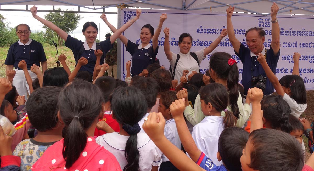 慈濟志工播放柬埔寨文的〈一家人〉,帶動小孩表演給家長們看。(攝影:陳誼謙)
