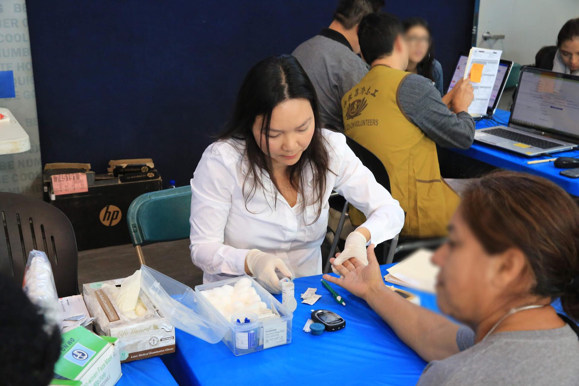 慈濟人醫會為民眾進行血糖檢測以追蹤健康。