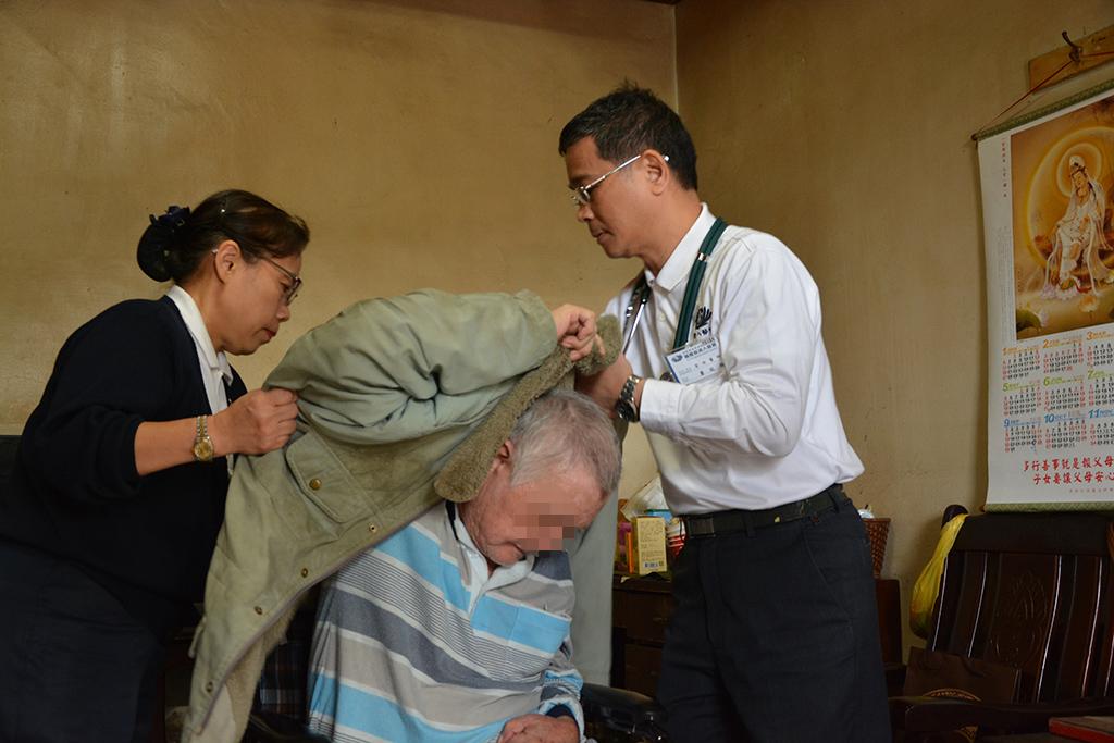 蕭瑞鵬醫師(右一)像家人一般,幫剛從床上起身的徐先生穿上外套,以免著涼。