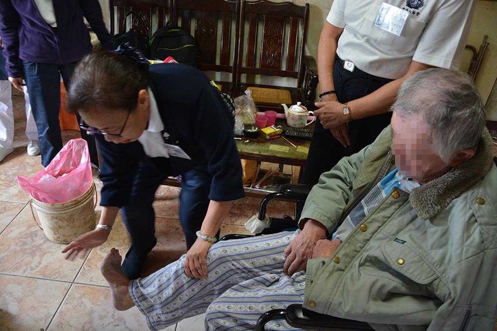 蘇瑋苓(左)一邊帶著徐先生做復健,一邊說:「我總是希望每次來,都能帶給他們一點東西,而不只是看看他們。」