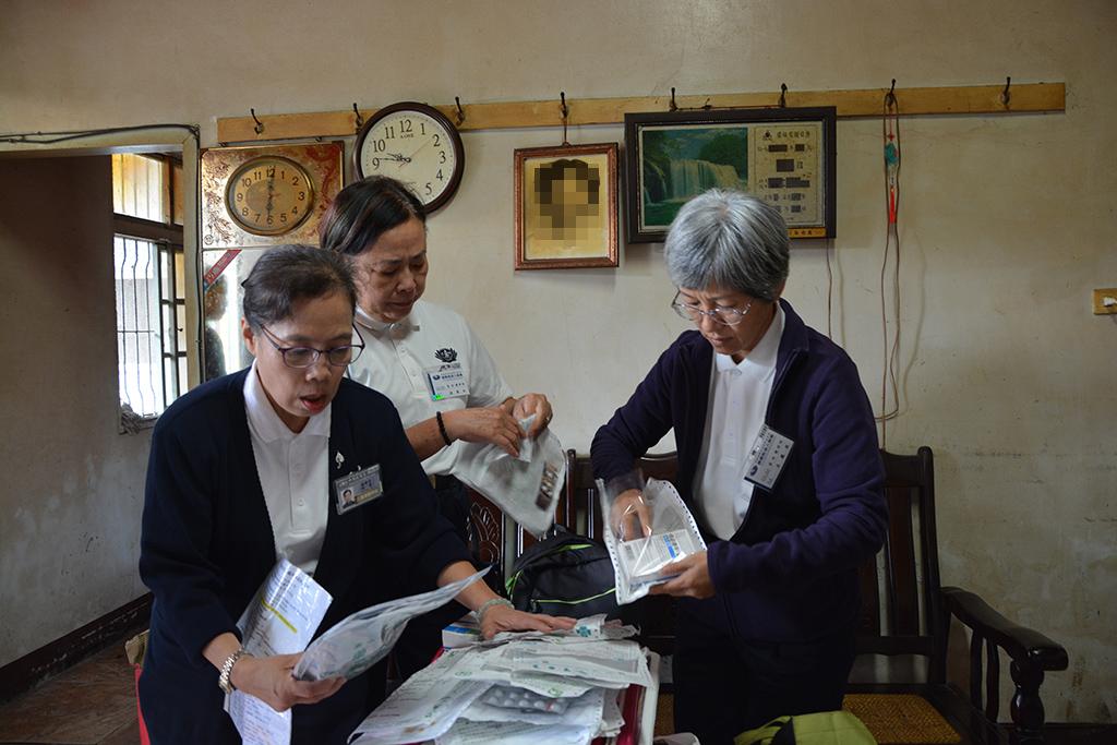蘇瑋苓(左)與同行的護理師林珠如(中)和呂鳳珠(右),三人一起將藥袋全部攤在桌子上,仔細檢視。