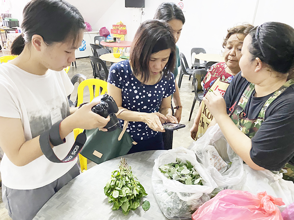 為了完成計畫,陳翎(左)拍攝600多張母國野菜等菜餚照片。