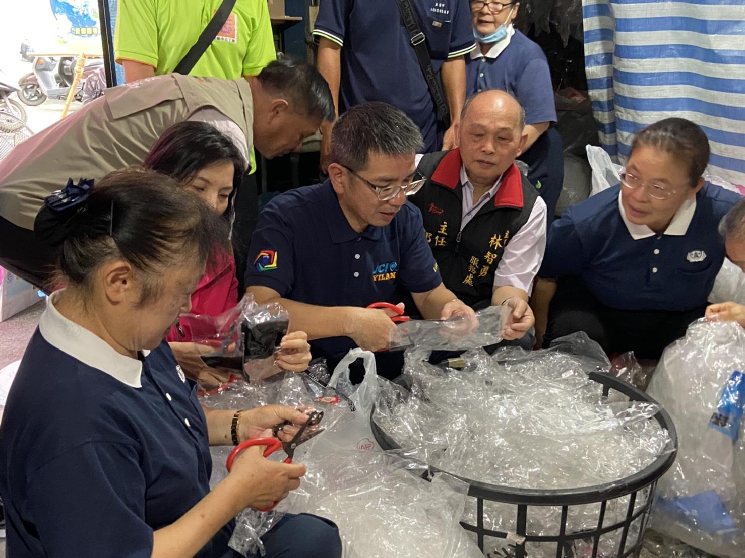 宜蘭市長江聰淵特地前往表揚,並親身體驗剪塑膠袋的工作。(慈濟基金會)