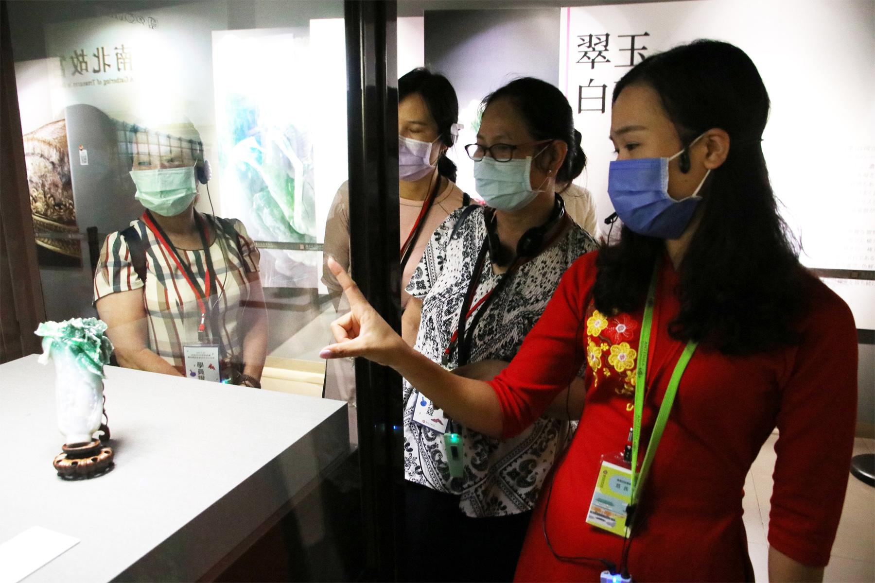 越南新住民范氏月(右1)指出翠玉白菜只有18公分高,但卻雕工精細,令人陶醉。
