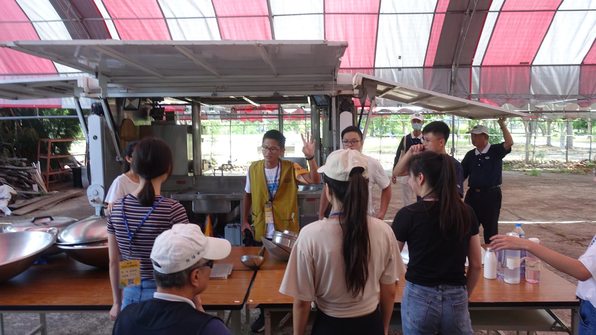 35歲的陳柏宏是餐廳大廚(著背心),帶領一群很少下廚的學員完成任務。