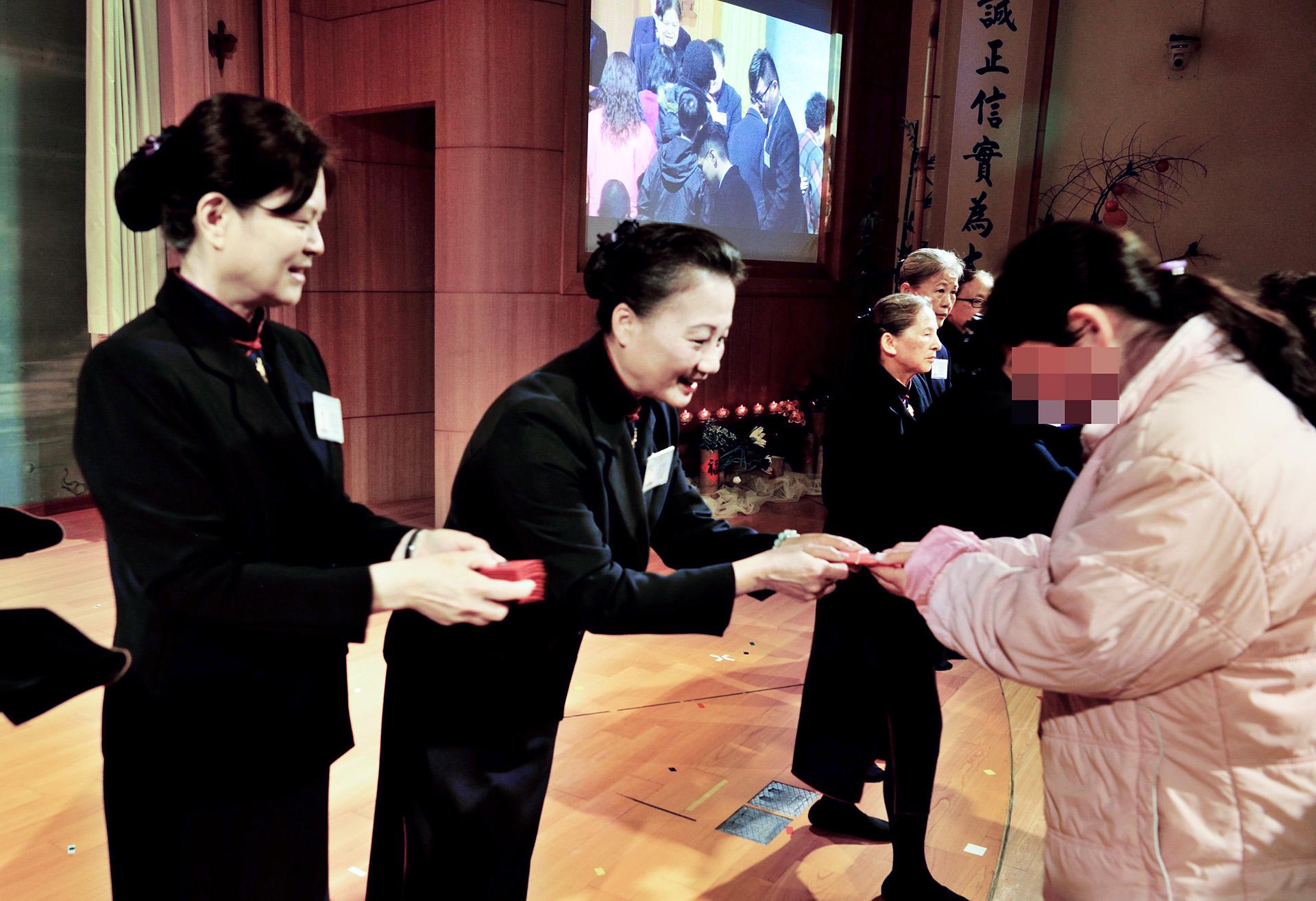 照顧戶、關懷戶從志工手中領到的福慧紅包,領受證嚴上人及精舍師父的祝福。