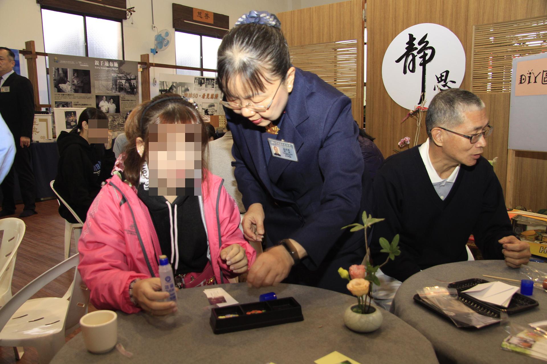 主責志工陳秀嫻陪伴張振華的女兒體驗DIY手做書籤,這也是女兒的興趣之一。