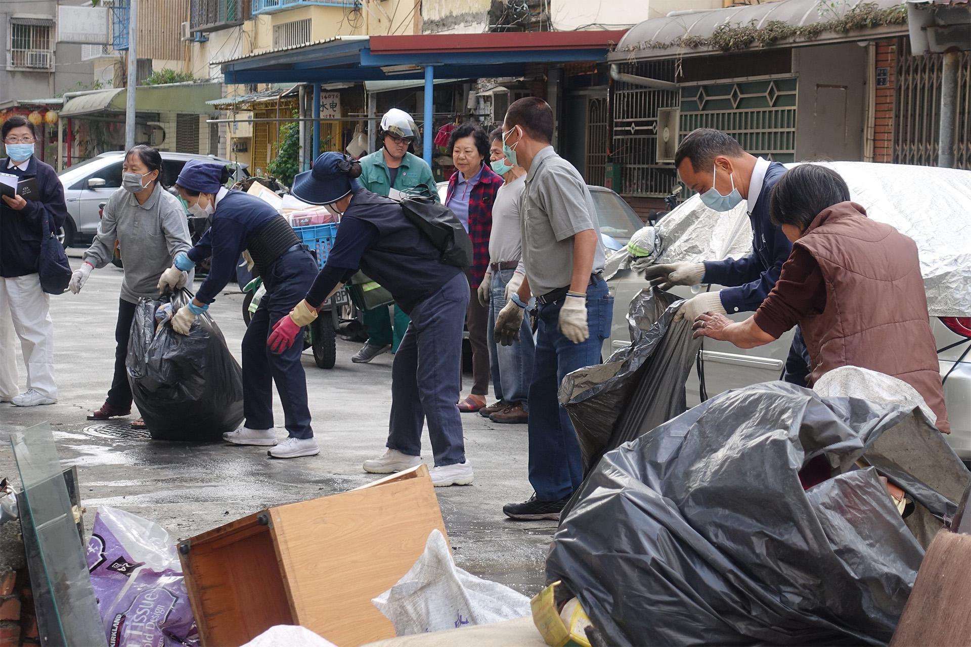 志工一手接一手,將其他小件家具、裝袋後的物品用人龍方式從樓上接到樓下。