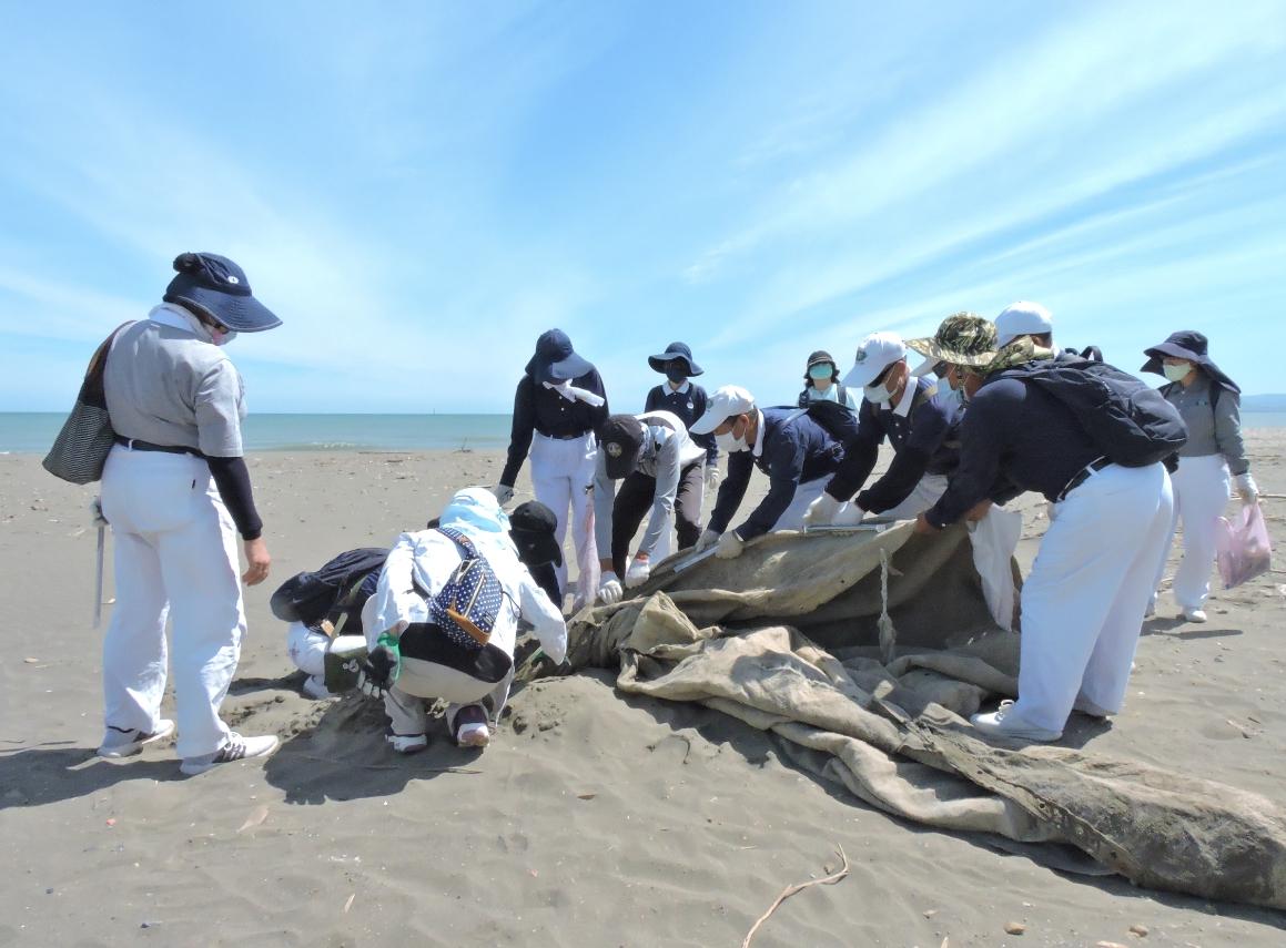 有大型垃圾被沙子掩埋極深,需要多名志工聯手如拔河般,費力將其從沙推當中移除。