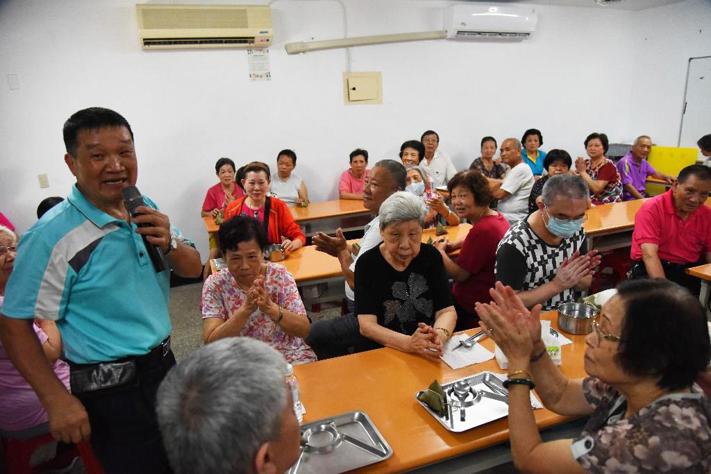張進國里長(左一)感恩慈濟志工幫忙布施心力,讓社區老人家提前過溫馨的端午佳節。
