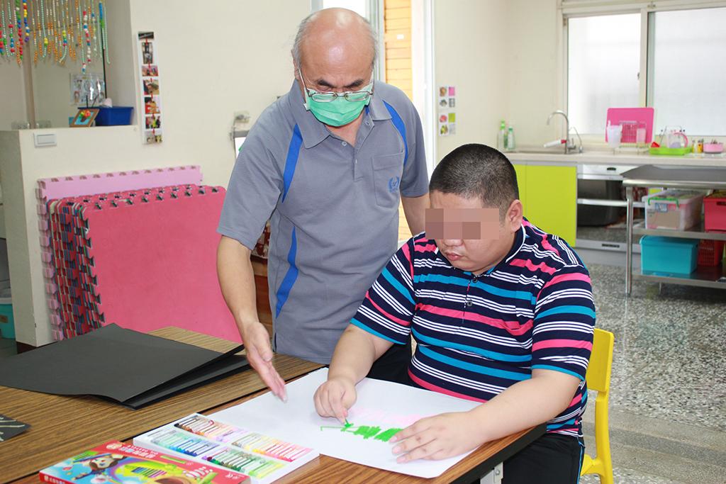 繪畫老師蘇健全(左)指導智青阿昌畫作。