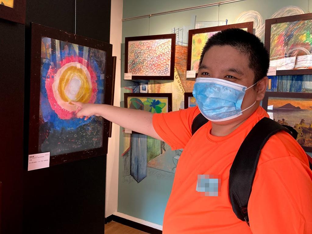 阿昌很開心看到自己的畫作被展出。