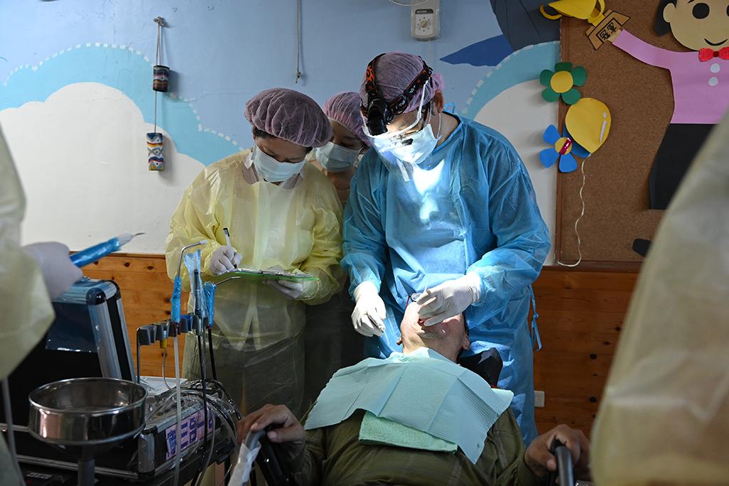 林聰勝醫師(右)一家三口再次到創世基金會臺東分院、慎修養護中心為住民洗牙。