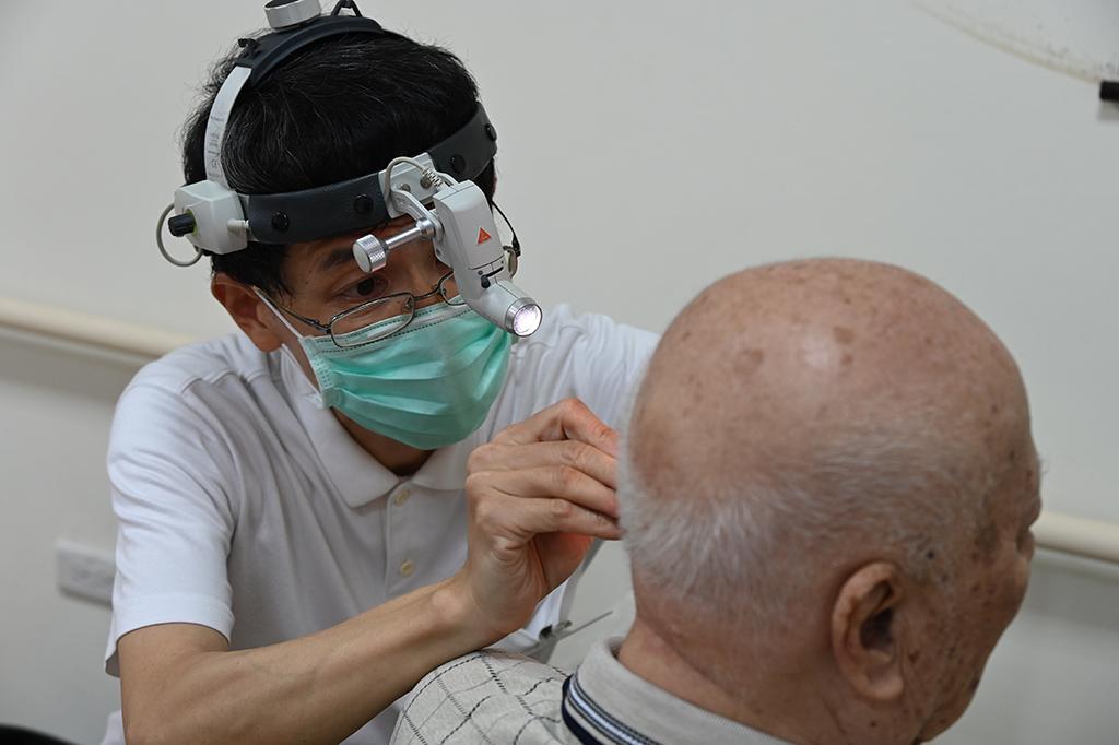 屏東慈濟人醫會黃正輝醫師幫仁愛之家的住民長者清理耳垢和檢查耳內健康情況。