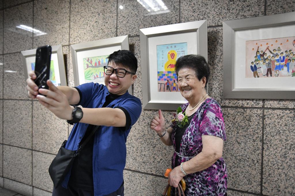 九十二歲的林江錦屏老太太和孫女張瓊云(左)祖孫情深,瓊云說阿嬤會邊畫畫邊哼歌,看到阿嬤的畫以阿嬤為榮。
