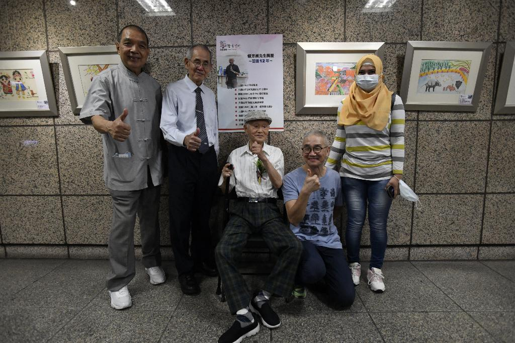 九十歲的賴芳洲先生(中)從銀行界退休,習畫十二年,由兒子賴宗禧(右二)陪伴來看展。