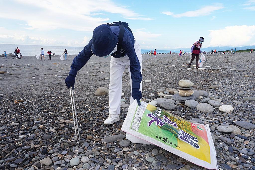 環保志工王齡珠彎腰夾起細小被石頭覆蓋的垃圾。