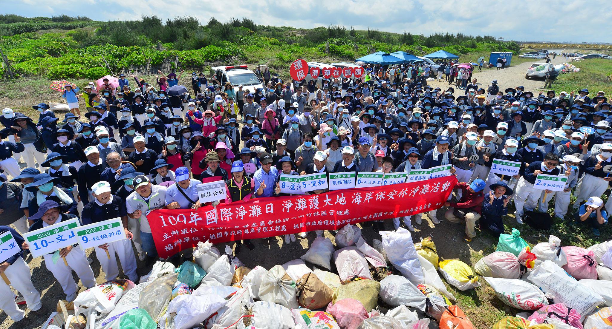 國際淨灘日,全體參與志工與民眾在清出的五千公斤垃圾前,宣示淨灘護大地。