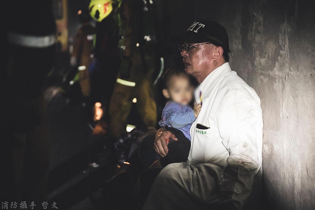 花蓮慈濟醫院骨科部主治醫師吳坤佶,在太魯閣號失事現場呵護年幼乘客的暖心畫面。(圖:救護義消蔡哲文授權提供)