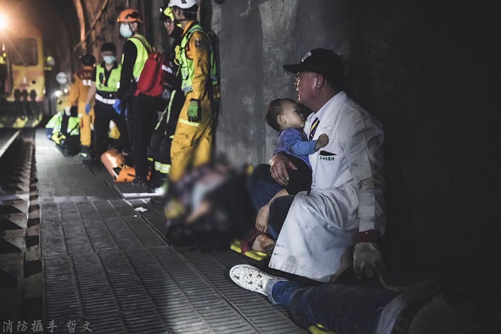 花蓮慈濟醫院骨科部主治醫師吳坤佶,在隧道內失事現場呵護年幼乘客的暖心畫面。(圖:救護義消蔡哲文授權提供)
