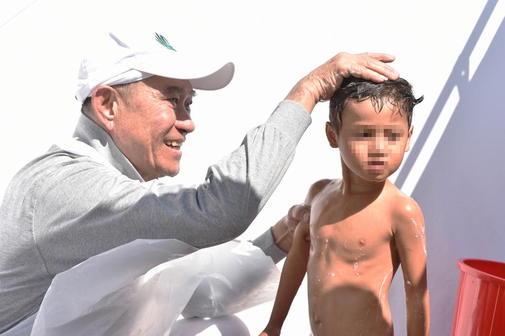 2017年,石漢秋參與柬埔寨金邊市朗哥垃圾掩埋場的大米發放暨義診活動時,為貧民窟的孩子洗澡。(攝/ 陳碧慧)