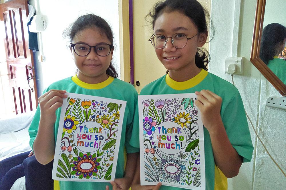 三個月的線上課輔計畫來到尾聲,大家一起連線,參與別開生面的歡樂感恩會。受惠學子愛麗莎(右)和妹妹庫萊莎(左)展示她們繪製的感謝信。