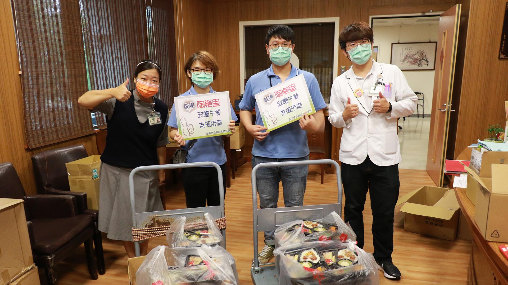 臺中慈濟醫院同仁手持感謝卡感恩送愛的商家。