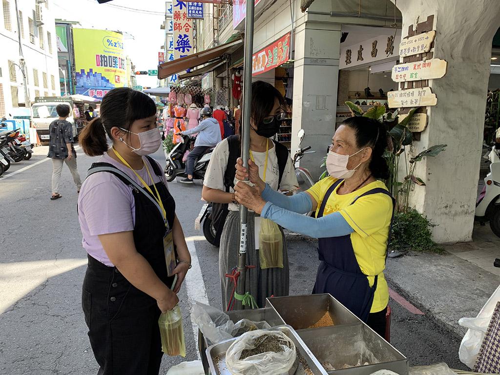 青年志工於屏東中央市場內和老店家採訪互動。