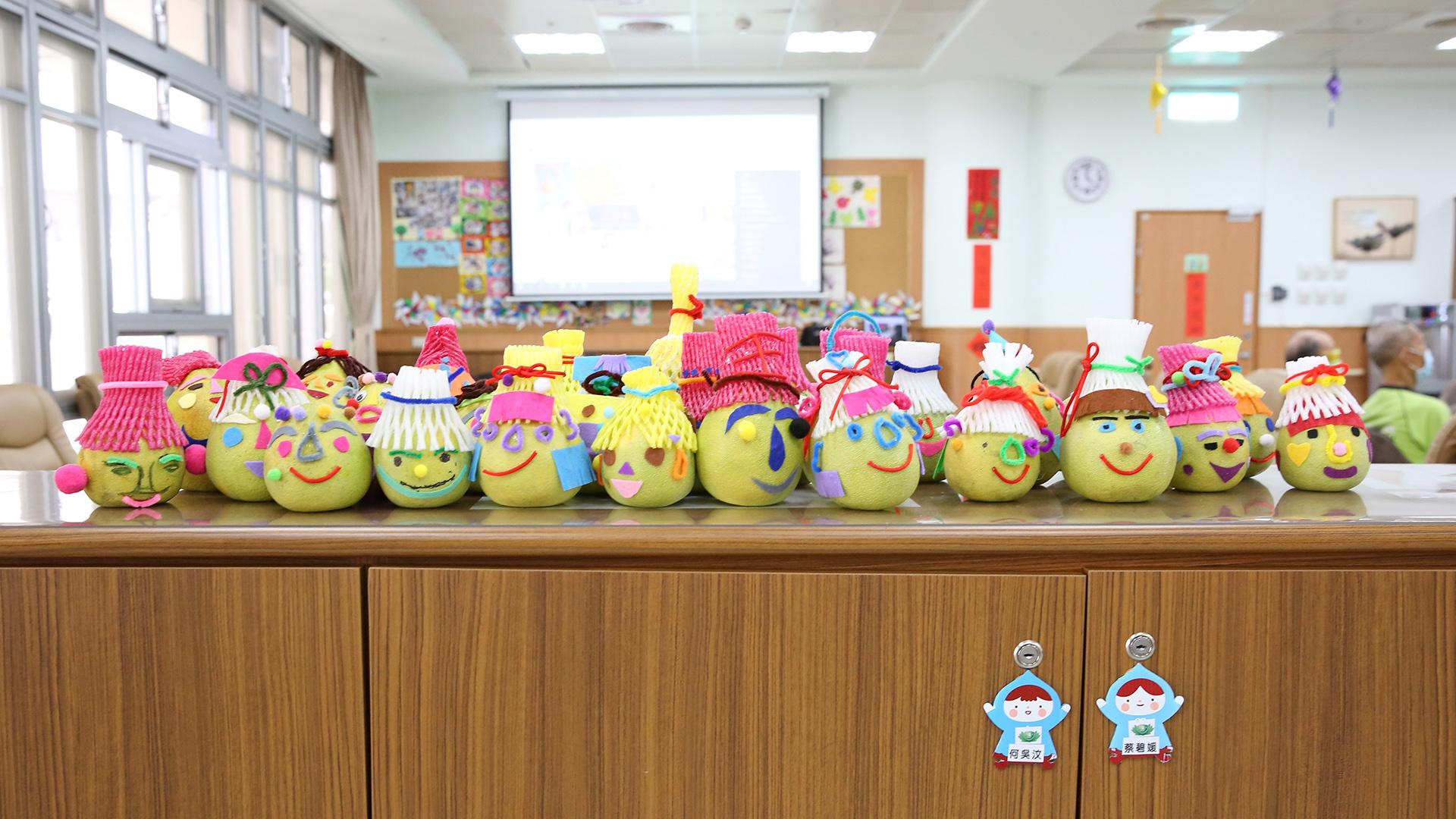 照顧團隊引導長輩們製作柚子娃娃,發揮創意拼出一張張可愛的笑臉。
