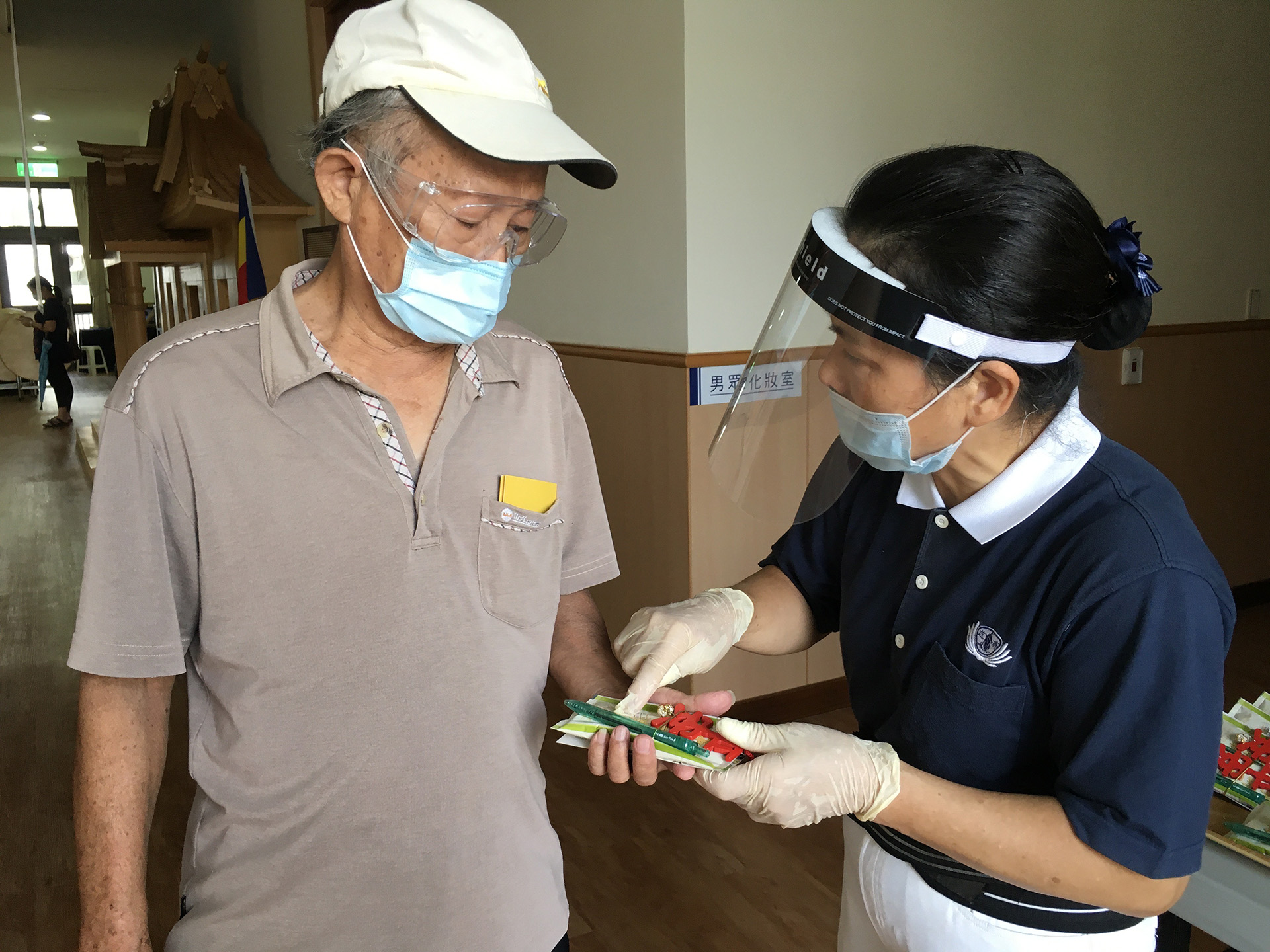 慈濟志工發送結緣品給接種後的民眾,圖為大甲靜思堂。