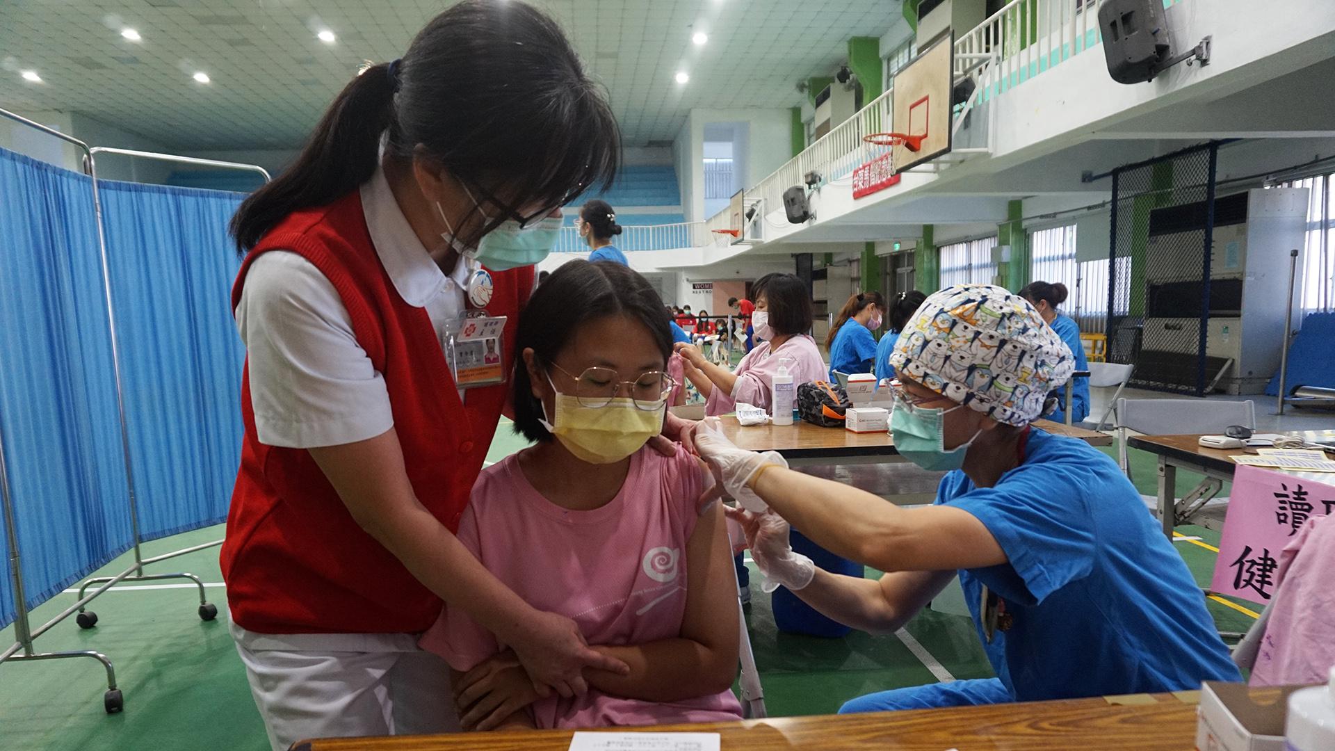 臺東馬偕醫院護理主任曾令君安撫正在接種疫苗的同學