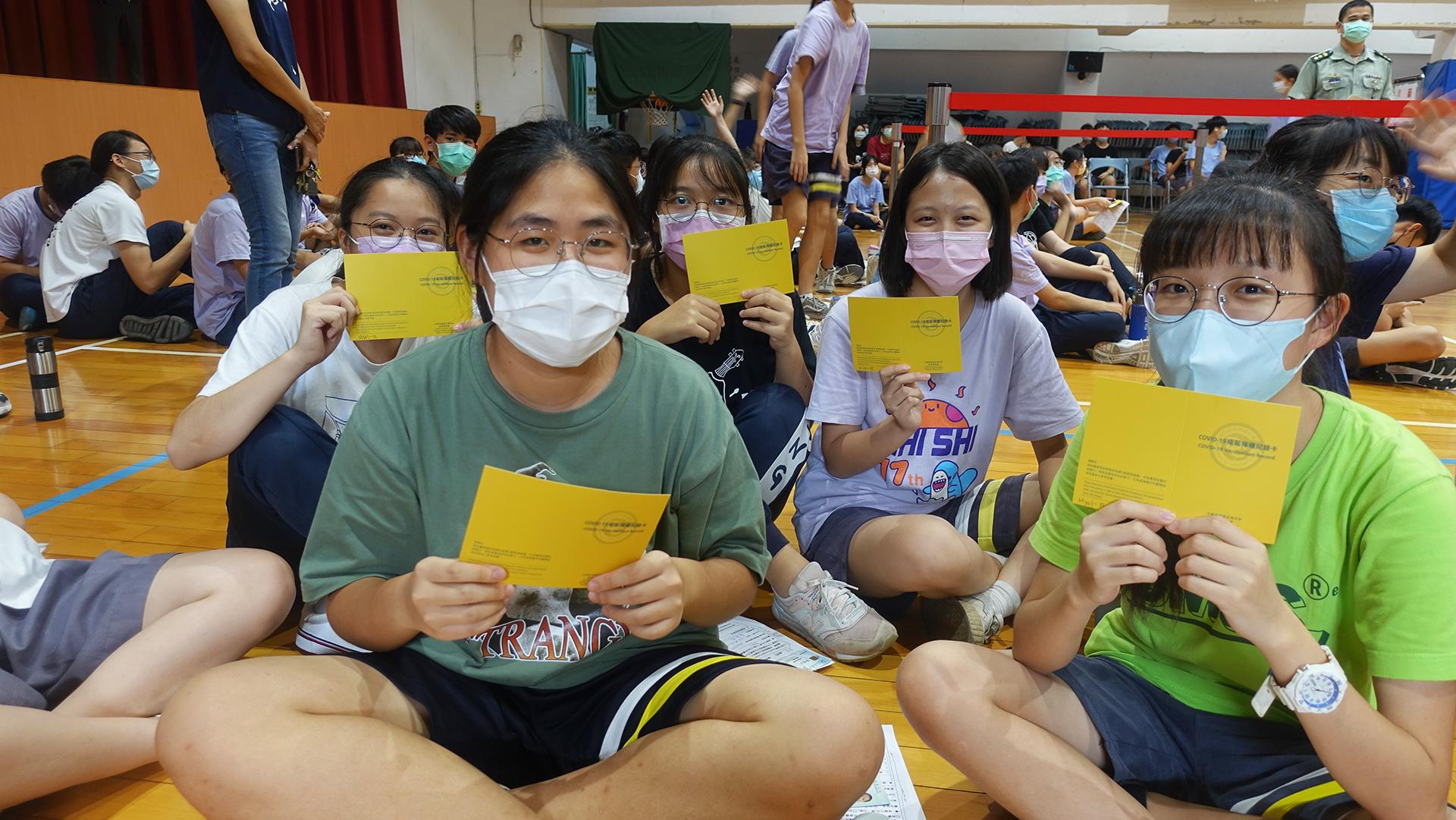 台中市9月23日起為全市高、國中學生進行BNT疫苗第一劑接種作業,同學等候時拿起Covid-19疫苗接種紀錄卡合影。